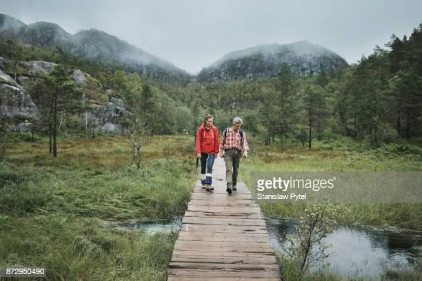 Two hikers passing through a brook on wooden bridge