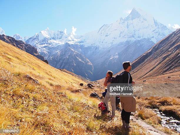 Two hikers rest on a clear day on the Annapurna Sanctuary Trail, with a view of Machapuchare in the background.