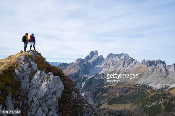 zwei wanderer stehen hoch oben mit herrlichem ausblick - spitze stock-fotos und bilder