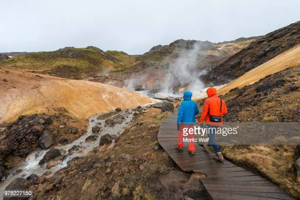 two hikers, steaming soil, seltun geothermal area, krysuvik volcano system, reykjanesfolkvangur national reserve, iceland - lava plain stock pictures, royalty-free photos & images
