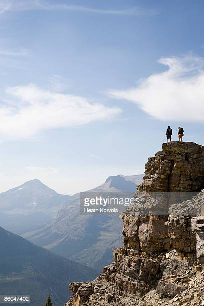 Two hikers take in the view from atop a mountain.