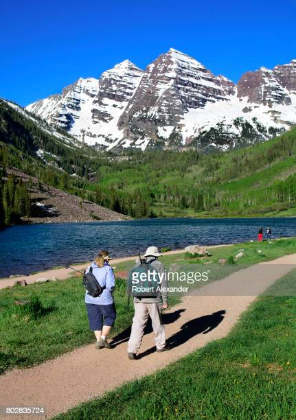 Two hikers walk past Maroon Lake with the Maroon Bells in the background The Maroon Bells near Aspen Colorado are two peaks in the Elk Mountains...