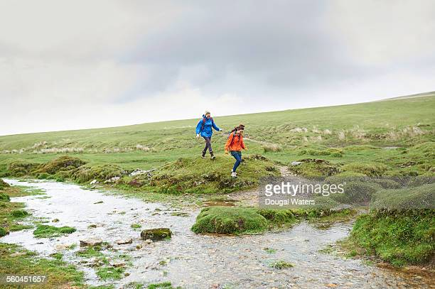 Two hikers walking along small stream