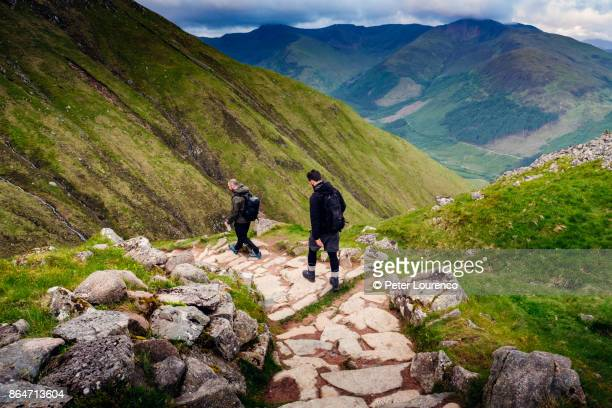two hikers walking down a path - grampian scotland stock pictures, royalty-free photos & images