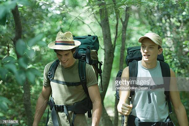 two hikers walking through forest - strap stock pictures, royalty-free photos & images