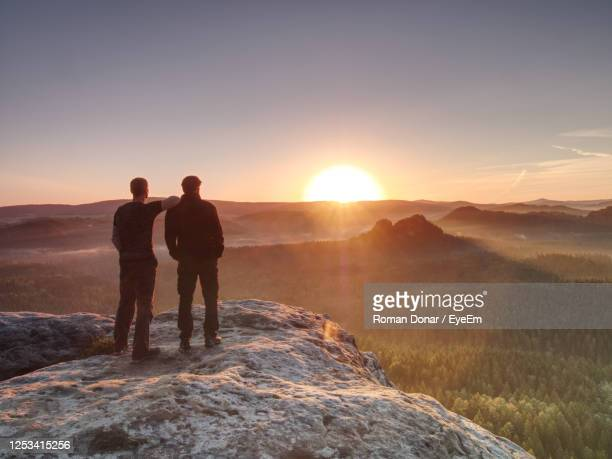 two hikers watch together amazing daybreak in mountains. men standing on mountain peak - animals in the wild stock pictures, royalty-free photos & images