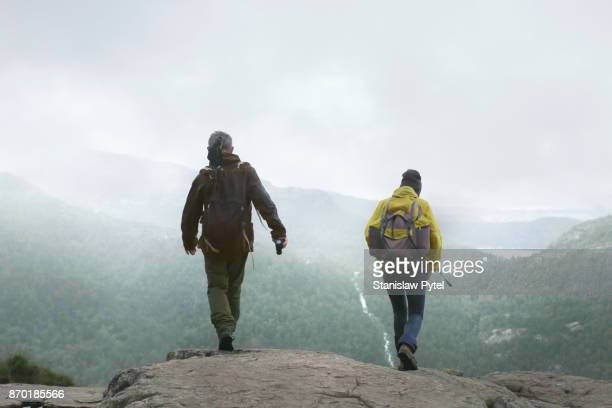 Two hikers with backpacks walking against forest and mountains