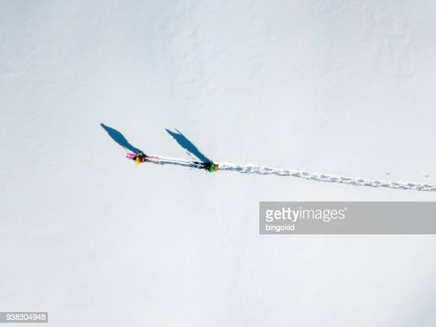 two hikers with long shadows walking over snow (aerial shot) - track imprint stock photos and pictures