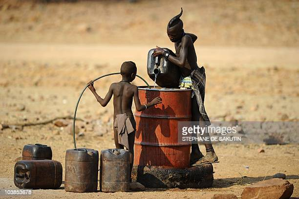 Two Himba boys pour water into a tank on August 20 2010 in the village of Okapare near Opuwo in northern Namibia AFP PHOTO / STEPHANE DE SAKUTIN