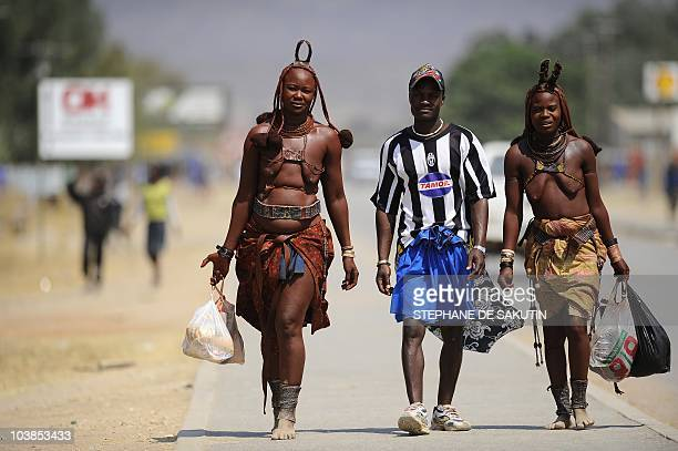 Two Himba women and a Himba man walk on August 21 2010 in the main street of Opuwo in northern Namibia AFP PHOTO / STEPHANE DE SAKUTIN