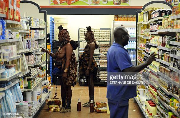 Two Himba women shop at a supermarket on August 18 2010 in Opuwo north of Namibia AFP PHOTO / STEPHANE DE SAKUTIN
