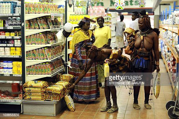 Two Himba women shop at a supermarket on August 18, 2010 in Opuwo, north of Namibia. AFP PHOTO / STEPHANE DE SAKUTIN