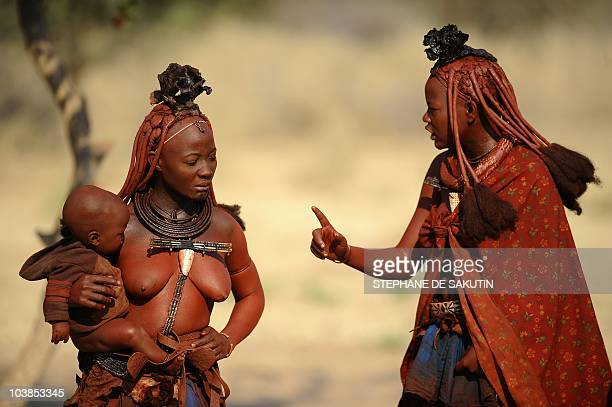 Two Himba women talk on August 19 2010 in the village of Ohungumure 15 kms west of Opuwo in northern Namibia AFP PHOTO / STEPHANE DE SAKUTIN