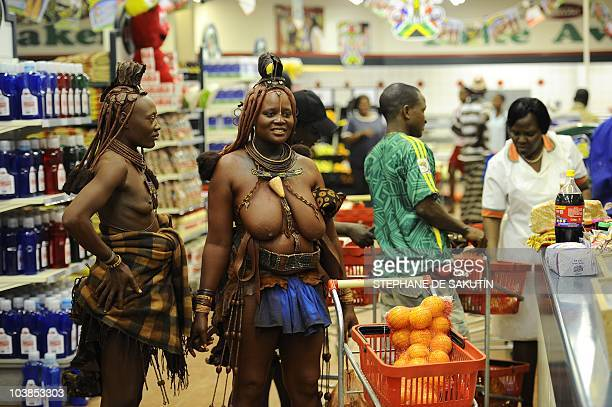 Two Himba women wait in line to pay for their shopping at a supermarket on August 18, 2010 in Opuwo, north of Namibia. AFP PHOTO / STEPHANE DE SAKUTIN