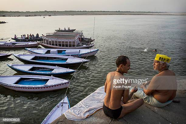 Two Hindu devotees talk after taking a dip on May 11 2014 on the Ganges River in Varanasi India Indians will vote in the ninth and final phase of a...