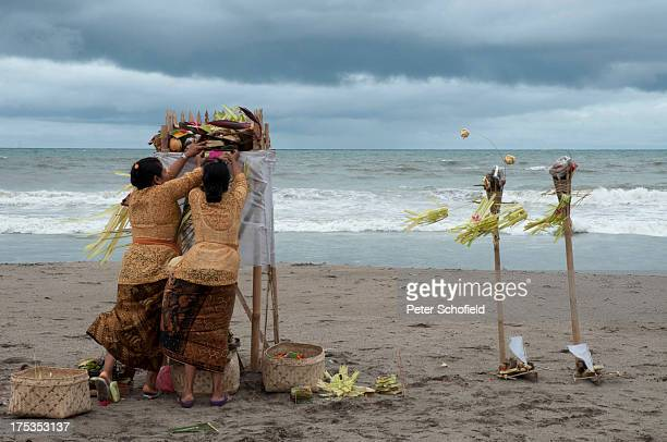 Two Hindu women struggle with the wind while giving thanks for their children on Seminyak Beach, Bali, Indonesia. The section of the beach is sacred...