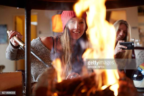 Two hip young women in cabin roasting smores