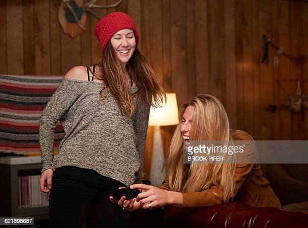 Two hip young women laughing in cabin