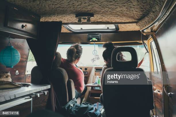 Two hippies, in their forties, sitting in their all equipped 1970's camper before heading onto a new adventure.