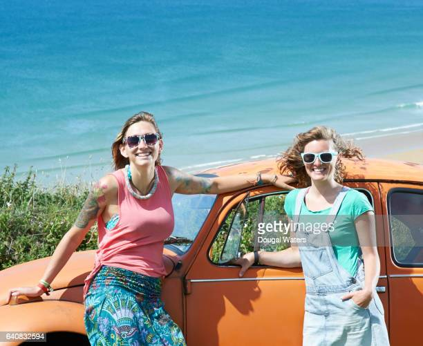 Two hipster friends on road trip with vintage car and beach.