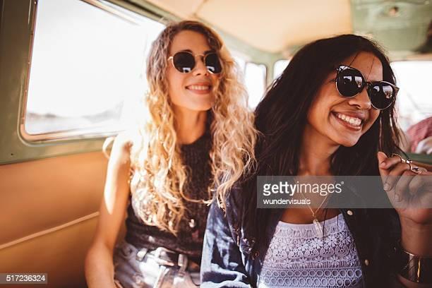 Zwei Hipster Mädchen lächelnd Freunde sitzen zusammen im Retro-Van