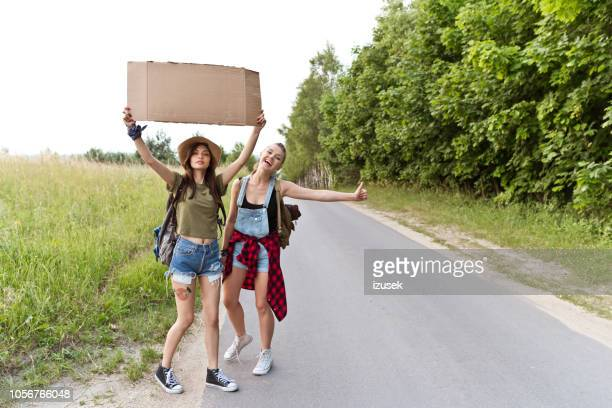 two hipster girls hitchhiking together - izusek stock pictures, royalty-free photos & images