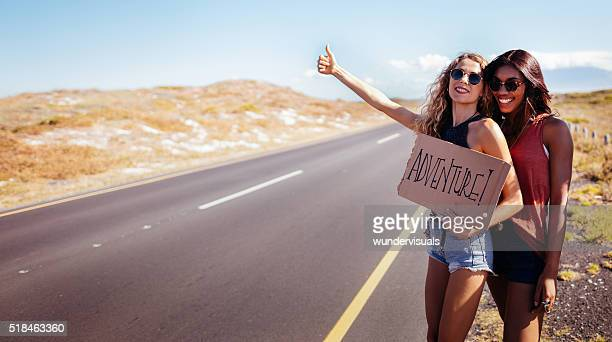 two hipster girls hitchhiking together - hitchhiking stock pictures, royalty-free photos & images