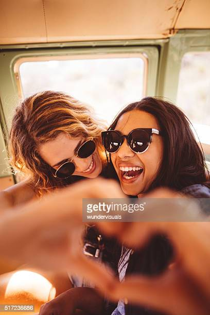Two Hipster Girls Posing for Photo Making Hand Heart