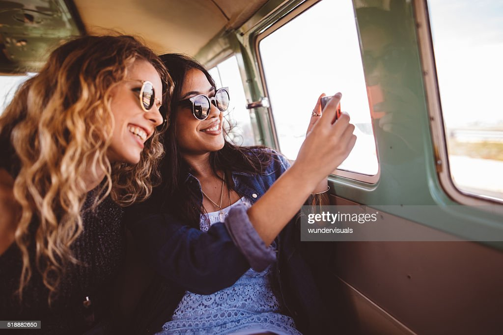 Two Hipster Girls Sitting Together taking a road trip photo : Stock Photo