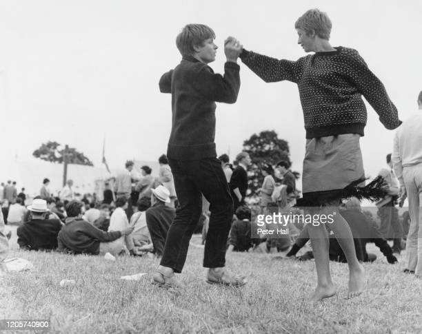 Two hipsters dancing in a public park during an event, circa 1965.