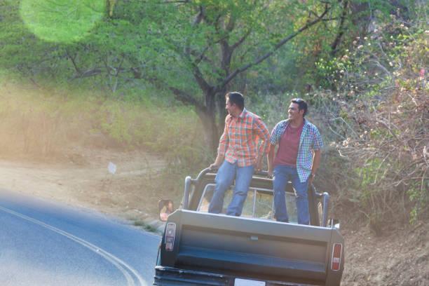 Two Hispanic Men Standing The Back of a Pick Up Truck Outside outside Mazatlán Sinaloa Mexico