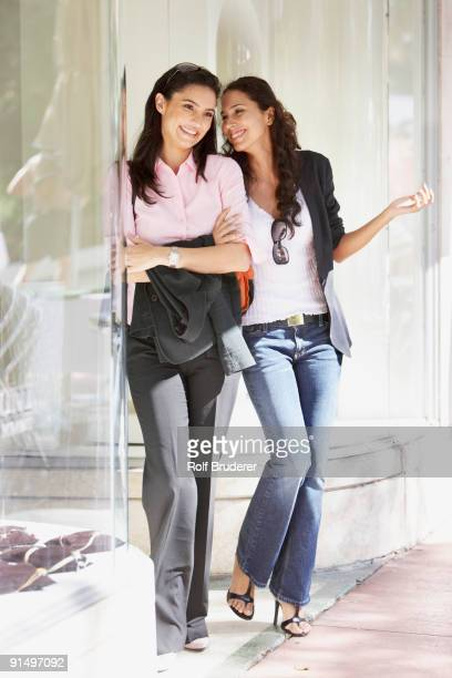 Two Hispanic woman next to store window