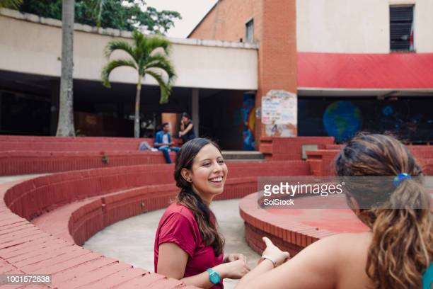 two hispanic women friends sitting together while laughing, in an urban area - cali colombia stock pictures, royalty-free photos & images
