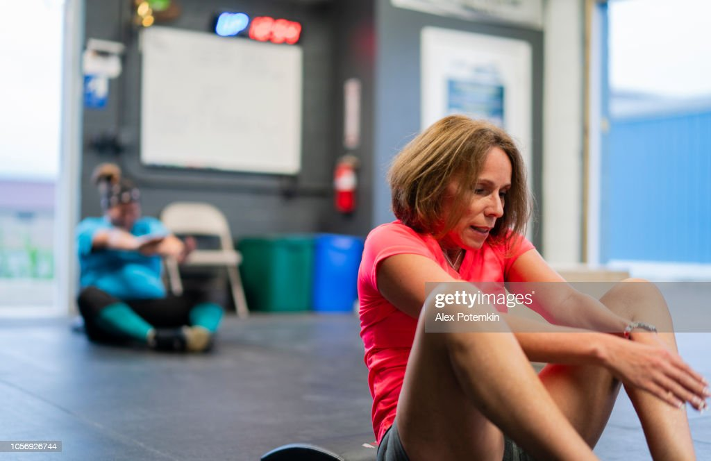 Two Hispanic women, the senior 55-years-old on the front and the young body-positive in the background, doing exercise in the gym : Stock Photo
