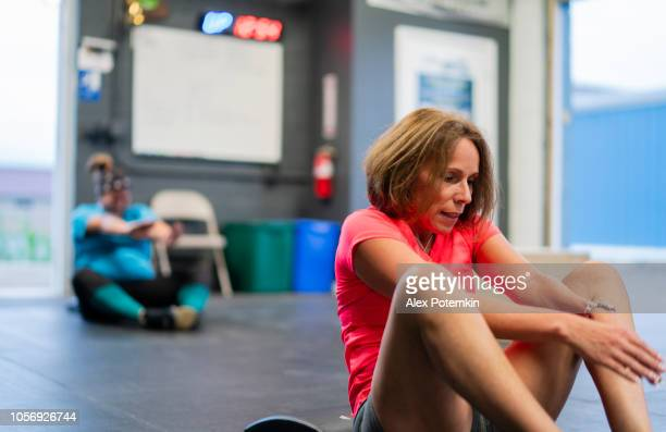 two hispanic women, the senior 55-years-old on the front and the young body-positive in the background, doing exercise in the gym - alex potemkin or krakozawr latino fitness stock photos and pictures