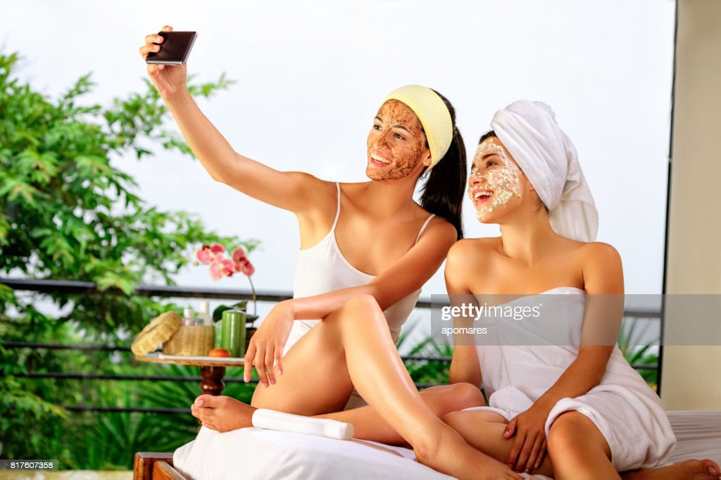 Two Hispanic young woman taking a selfie while doing beauty treatments at home or spa. : Stock Photo
