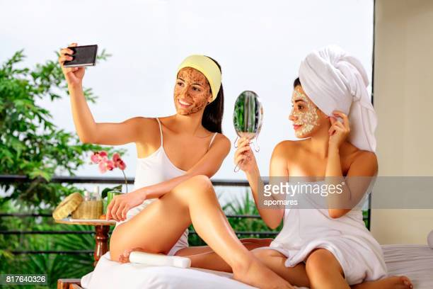 Two Hispanic young woman taking a selfie while doing beauty treatments at home or spa.