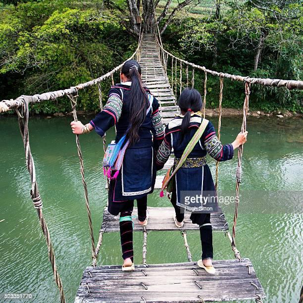 two hmong girls crossing a rope bridge in sapa, vietnam - hugh sitton stock-fotos und bilder
