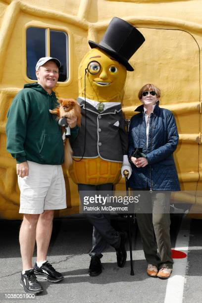Two hockey fans pose for a photograph with Mr Peanut at the Kraft Hockeyville Community Celebration during the NHL Kraft Hockeyville USA on September...