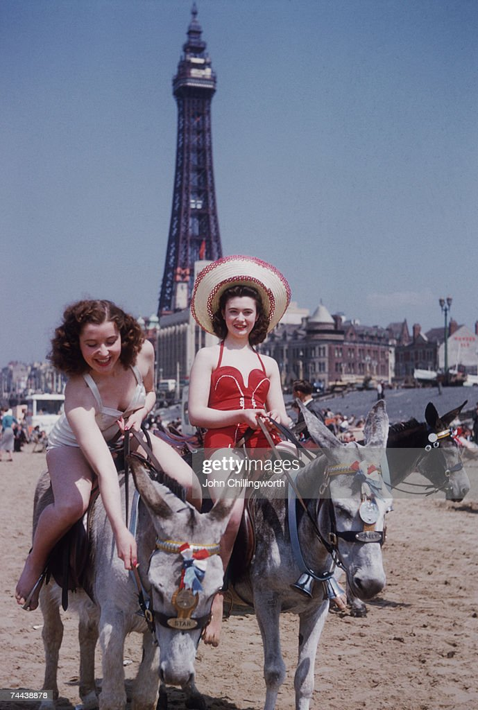Two holidaymakers enjoying a donkey ride on the beach at Blackpool, circa 1950. Blackpool Tower is in the background. Original Publication : Picture Post - 7227 - Blackpool - pub. 1954