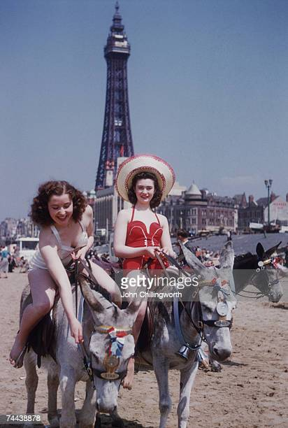 Two holidaymakers enjoying a donkey ride on the beach at Blackpool, circa 1950. Blackpool Tower is in the background. Original Publication : Picture...