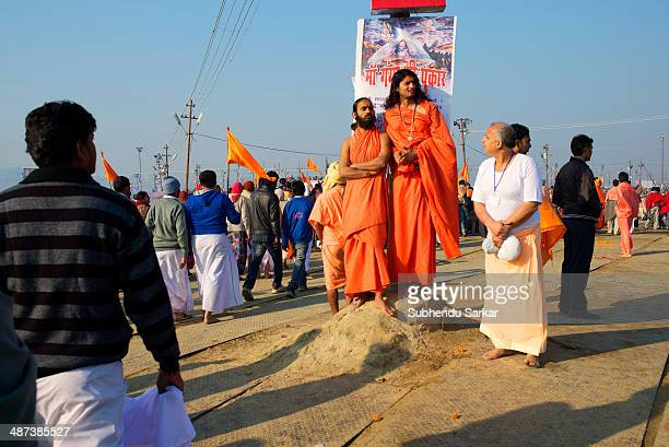 Two holy men stand on the Kumbh mela grounds. Kumbh Mela is a site of mass pilgrimage in which Hindus gather at a sacred river for a holy dip. It is...