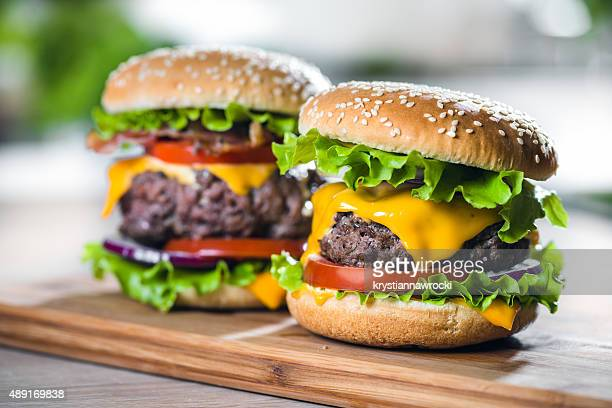 two home made huge cheeseburger on oak chopping board - cheeseburger stock pictures, royalty-free photos & images
