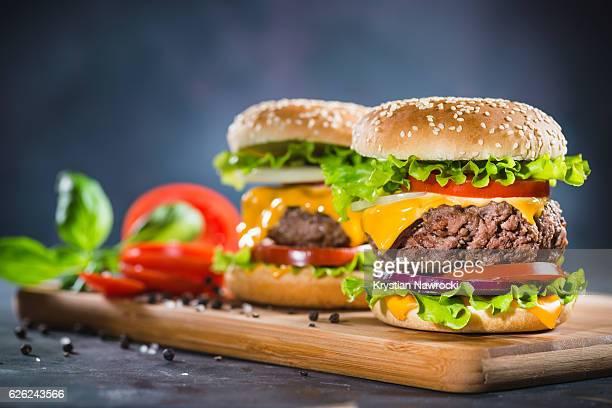 dois casa feito enormes cheesebúrguer em carvalho tábua de cortar - dois objetos - fotografias e filmes do acervo