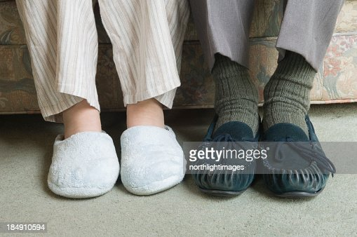 Two Home Slippers Worn By People Sitting On The Couch ...