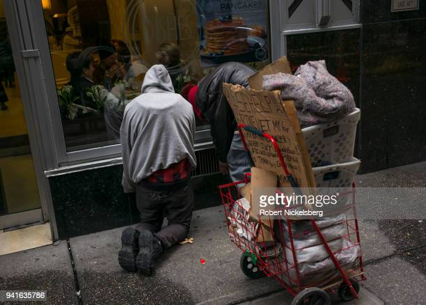 Two homeless men one a former Marine veteran warm themselves in front of a restaurant's heating duct April 2 2018 in New York City There are...
