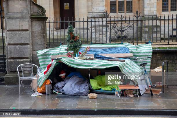 Two homeless men sleeping under a makeshift tent with festive decorations on Christmas Eve on the 24th December 2019 in Oxford in the United Kingdom....