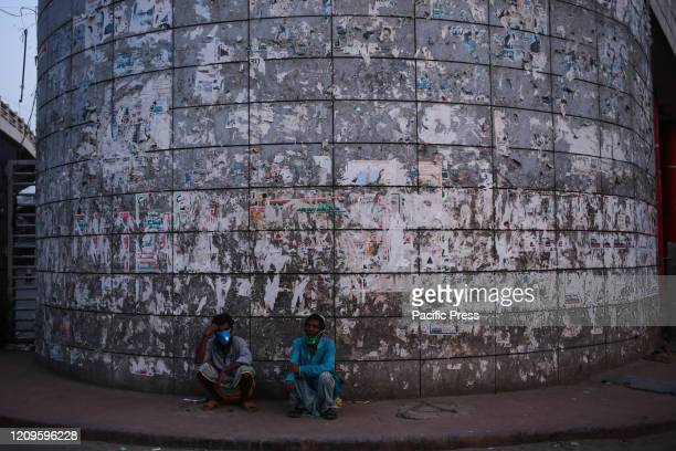 Two homeless people are sitting in front of Baitul Mukarram the national mosque of Bangladesh during the pandemic situation caused by CoVid19