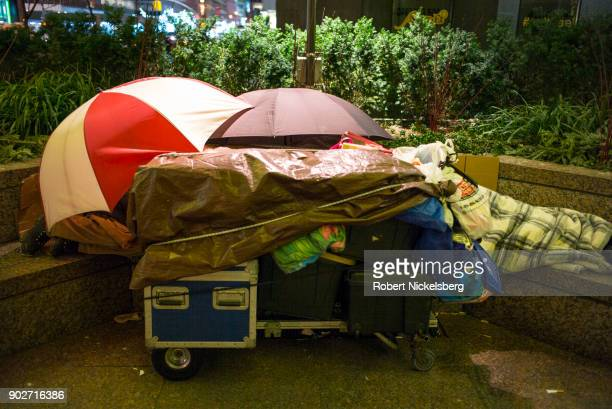 Two homeless people sleep on a granite bench in freezing temperatures at 12F on December 28 2017 in New York City According to Coalition for the...