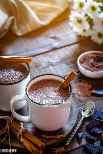 Dos tazas de chocolate caliente caseras en mesa de madera rústica